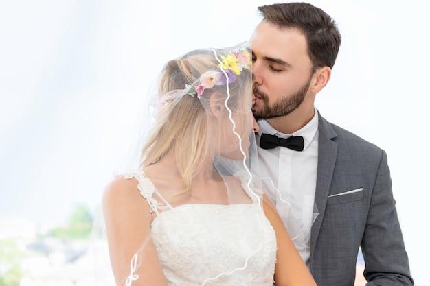 Casal de noivos caucasiano beijo e abraço no estúdio de casamento.