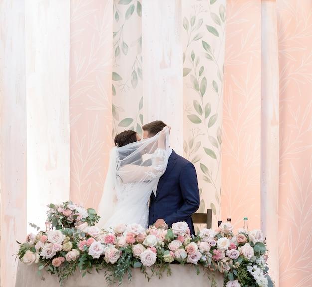 Casal de noivos coberto com véu está beijando ao lado da mesa de casamento decorada com rosas