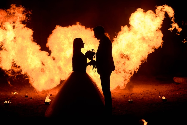 Casal de noivos com arte de cara de caveira está de pé no escuro