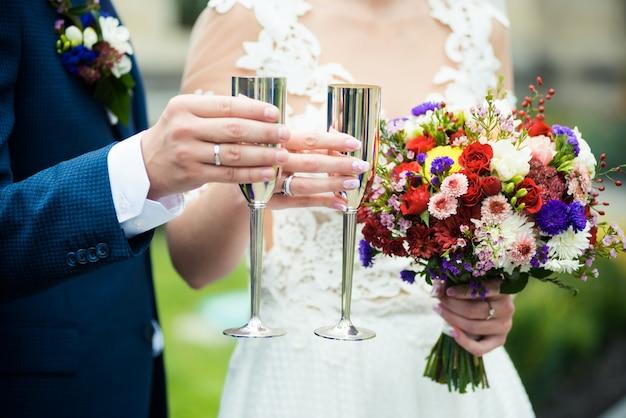 Casal de noivos com buquê de casamento e champanhe