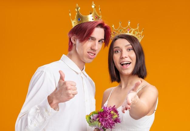 Casal de noivos com buquê de flores em vestido de noiva usando coroas de ouro sorrindo alegremente posando juntos mostrando thums em pé sobre uma parede laranja