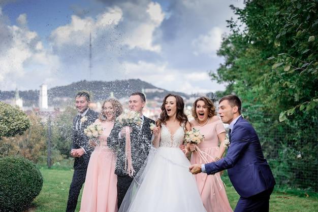 Casal de noivos com melhores amigas está comemorando o dia do casamento ao ar livre com derramar champanhe