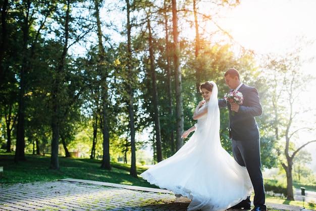 Casal de noivos dançando no parque
