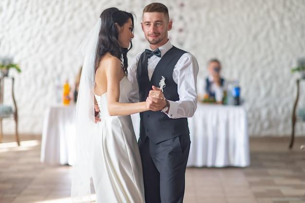 Casal de noivos dançando sua primeira dança no restaurante.