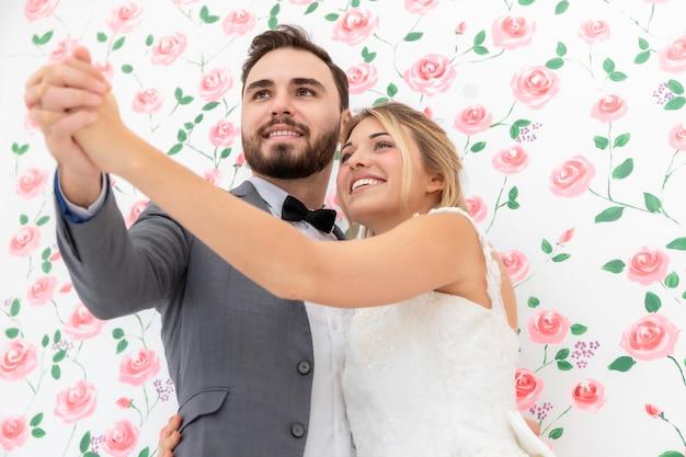Casal de noivos de caucasiano dançando e brincando no estúdio de casamento.