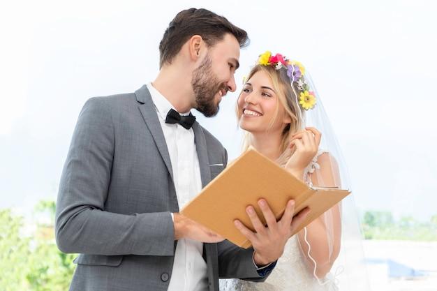 Casal de noivos de caucasiano escolhendo vestido no estúdio de casamento.