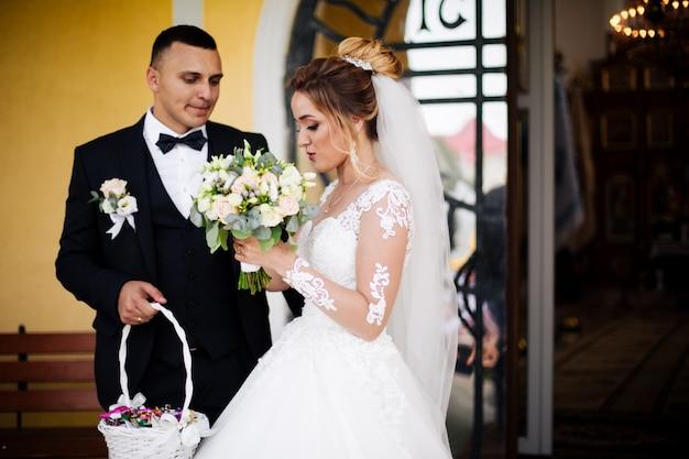 Casal de noivos dentro de casa está se abraçando. menina linda modelo de vestido branco. homem de terno. noiva de beleza com noivo