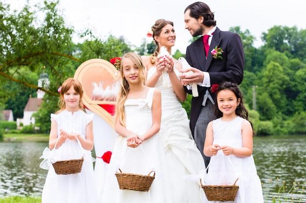 Casal de noivos e filhos de flores com pombas