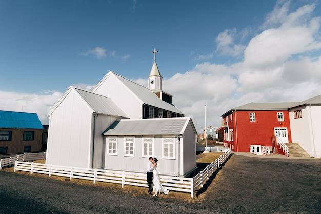 Casal de noivos em frente a uma igreja de madeira na islândia