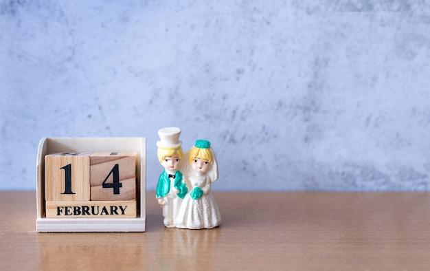 Casal de noivos em miniatura com calendário de madeira, 14 de fevereiro. dia dos namorados