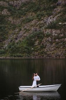 Casal de noivos em pé abraçando em um barco no lago