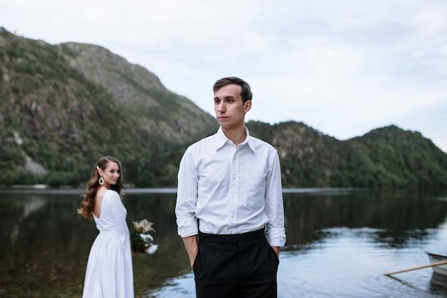 Casal de noivos em pé na margem do lago