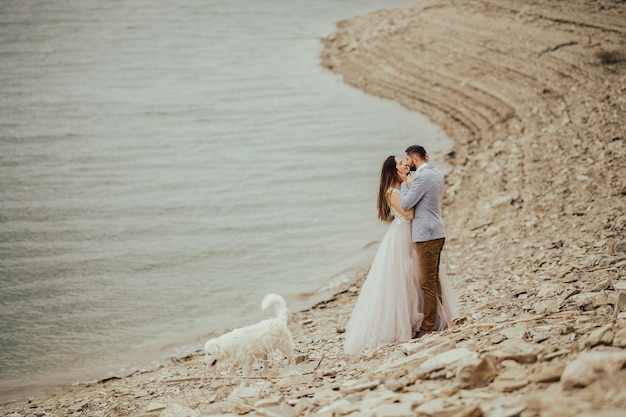 Casal de noivos em pé na margem do rio admirando a bela paisagem montanhosa
