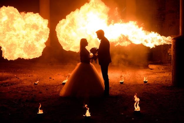 Casal de noivos em trajes medievais com maquiagem estilo vampiro em pé no escuro