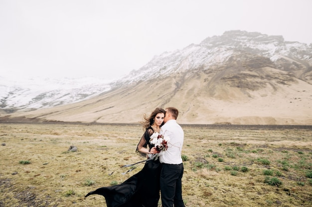 Casal de noivos em um fundo de montanhas nevadas, a noiva em um vestido preto e o noivo estão se abraçando