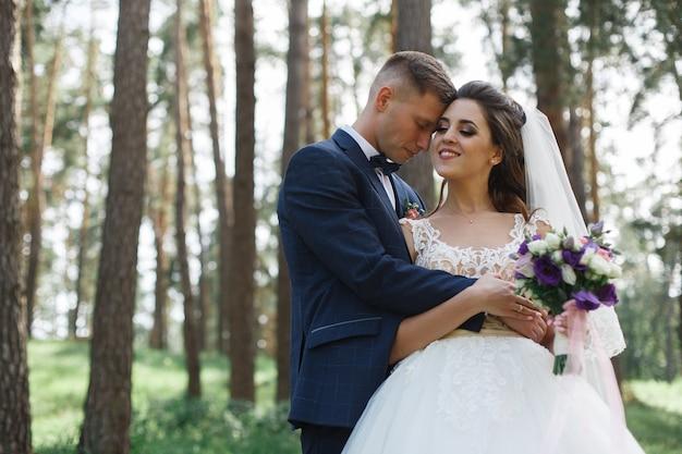 Casal de noivos emocional no parque verde na primavera. sorrindo a noiva e o noivo em dia de sol ao ar livre. noivos felizes abraçando e beijando no dia do casamento na natureza.