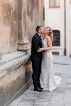 Casal de noivos está beijando ao ar livre perto da parede, feliz casal sorriu, loucamente apaixonado