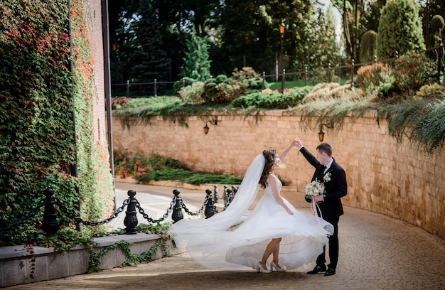 Casal de noivos está dançando perto de muro de pedra coberto de hera verde