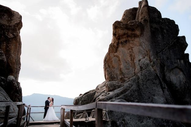 Casal de noivos está de pé na ponte de madeira entre dois penhascos altos e beijos, aventura de casamento