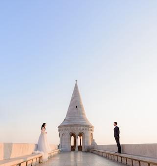 Casal de noivos está de pé separadamente em um lindo dia de verão leve