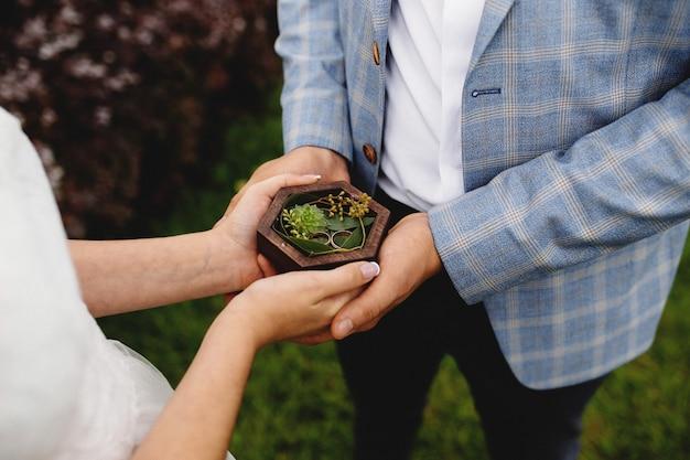 Casal de noivos está segurando seus anéis de casamento. foto de alta qualidade