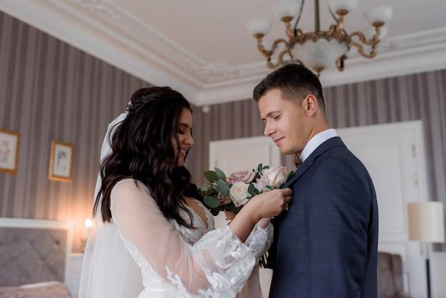 Casal de noivos estão se preparando juntos para a cerimônia de casamento com molho na flor na lapela