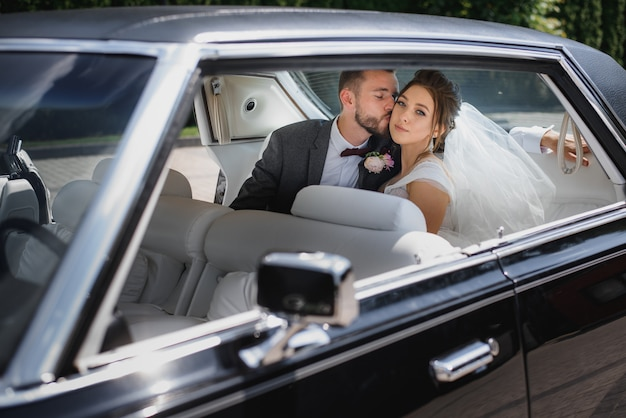 Casal de noivos estão sentados no banco de trás de um carro e beijando