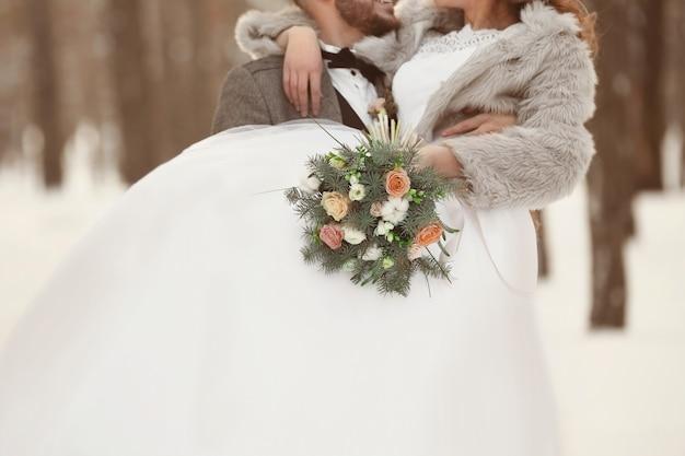 Casal de noivos feliz com buquê ao ar livre no dia de inverno