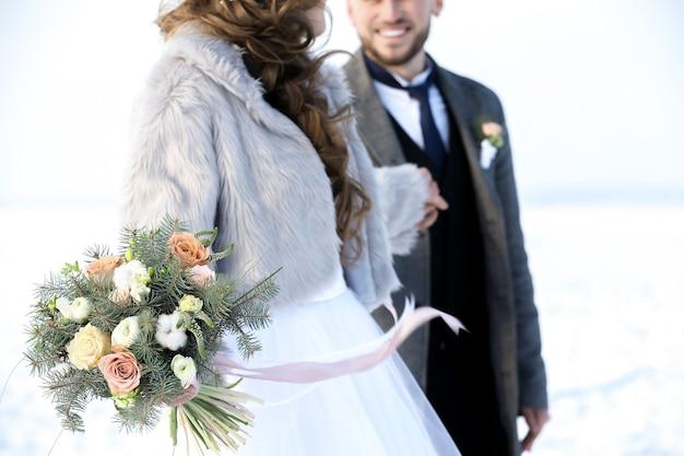 Casal de noivos felizes ao ar livre em um dia de inverno.