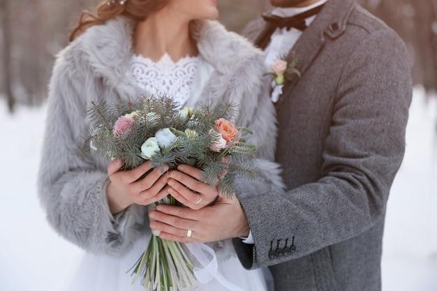 Casal de noivos felizes com buquê ao ar livre no dia de inverno, closeup