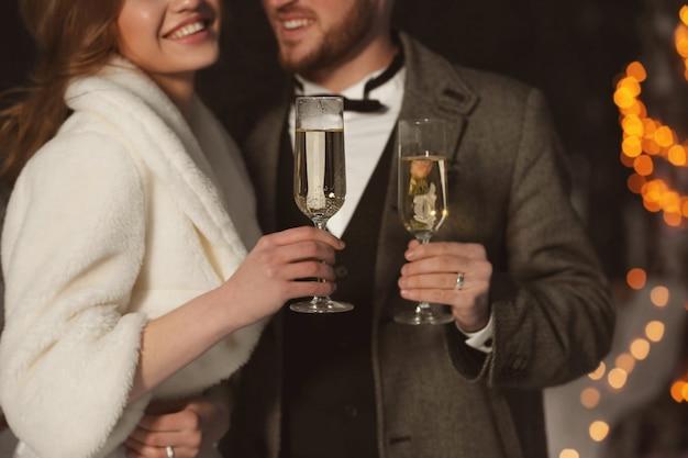 Casal de noivos felizes com taças de champanhe na noite de inverno, closeup