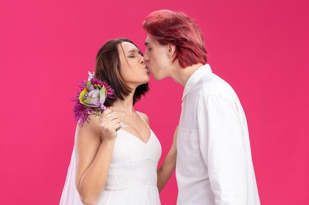Casal de noivos felizes em um vestido de noiva com flores felizes e apaixonados se beijando em pé sobre uma parede rosa