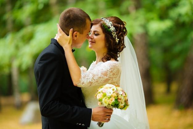 Casal de noivos. linda noiva e noivo. casado agora mesmo. fechar-se. noiva e noivo no casamento abraçando. noivo e noiva em um parque. vestido de casamento. casamento nupcial, outono