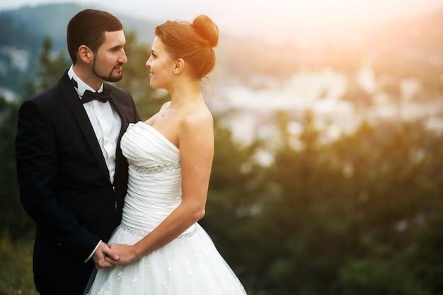 Casal de noivos na natureza, a cidade de distância