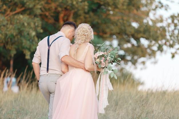 Casal de noivos na natureza em dia de verão. a noiva e o noivo caminhando