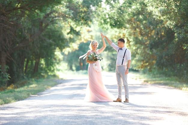 Casal de noivos na natureza em dia de verão. a noiva e o noivo dançando