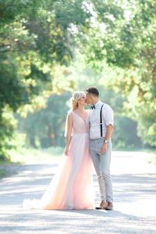 Casal de noivos na natureza em dia de verão. a noiva e o noivo se abraçando e se beijando