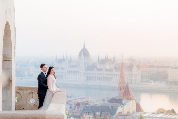 Casal de noivos na varanda de pedra de um antigo edifício histórico com vista deslumbrante de budapeste