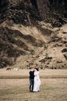 Casal de noivos no fundo de uma montanha rochosa e cavalos pastando na islândia a noiva e