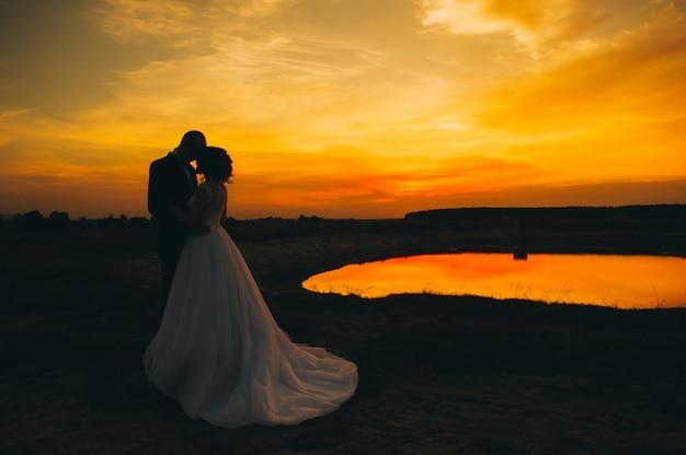 Casal de noivos no fundo do pôr do sol