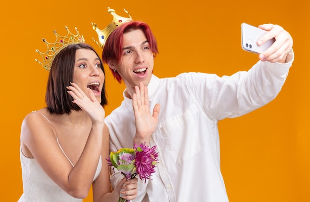 Casal de noivos noivo e noiva com buquê de flores em vestido de noiva usando coroas de ouro sorrindo alegremente fazendo selfie usando smartphone acenando com as mãos