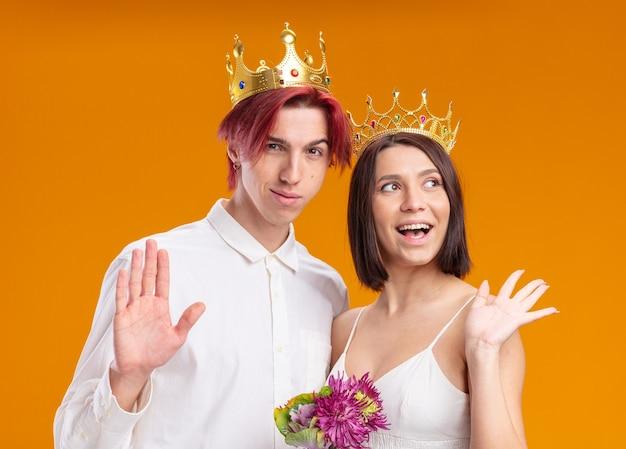 Casal de noivos, noivo e noiva com buquê de flores em vestido de noiva usando coroas de ouro sorrindo alegremente posando juntos