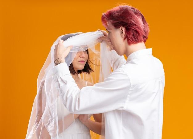 Casal de noivos, noivo e noiva com vestido de noiva sob o véu, noivo dando primeiro olhar para a noiva
