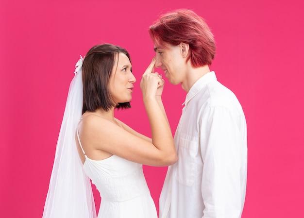 Casal de noivos, noivo e noiva em vestido de noiva branco, felizes e apaixonados, olhando um para o outro