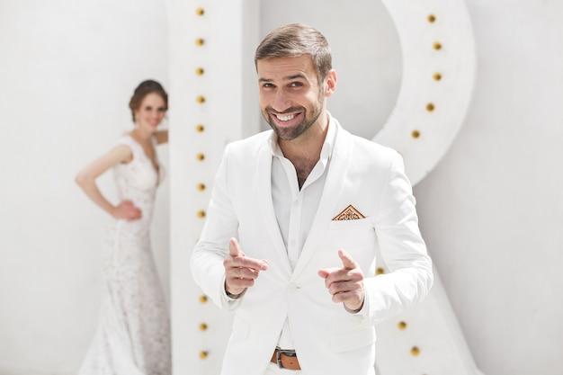 Casal de noivos, noivo e noiva posando em um estúdio branco
