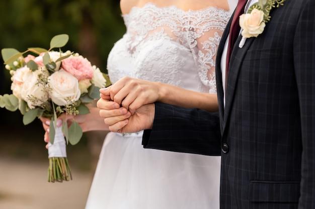 Casal de noivos, noivos de mãos dadas, lindo dia do casamento