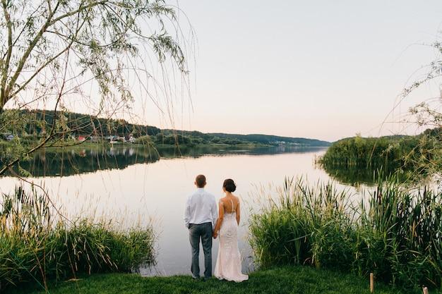 Casal de noivos olhando grande lago ao pôr do sol