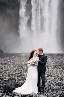 Casal de noivos perto da cachoeira de skogafoss, destino, islândia, casamento, casamento, noivo, abraços, noiva,