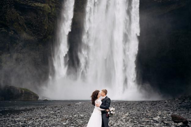 Casal de noivos perto da cachoeira de skogafoss, destino, islândia, casamento, casamento, noivo, beijo, noiva