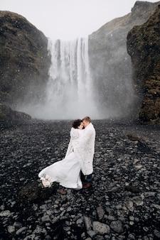 Casal de noivos perto da cachoeira skogafoss os noivos cobertos com um cobertor de lã onde